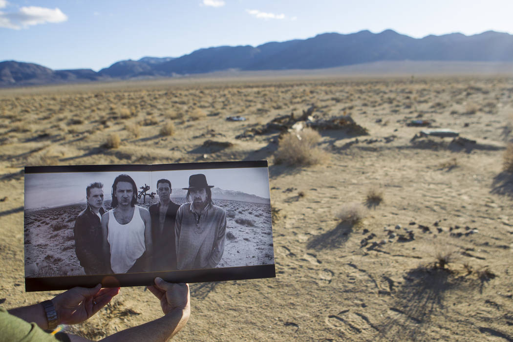"""The remains of the tree featured in the album artwork of U2's 1987 album """"The Joshua Tree"""" is shown with a copy of the album outside of Death Valley National Park along Californi ..."""