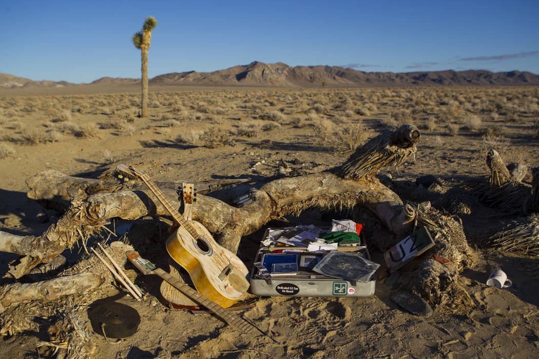 "A briefcase with tributes and memorabilia from fans of rock band U2 sits with the fallen tree that appeared in the band's 1987 album ""The Joshua Tree"" outside of Death Valley Nat ..."
