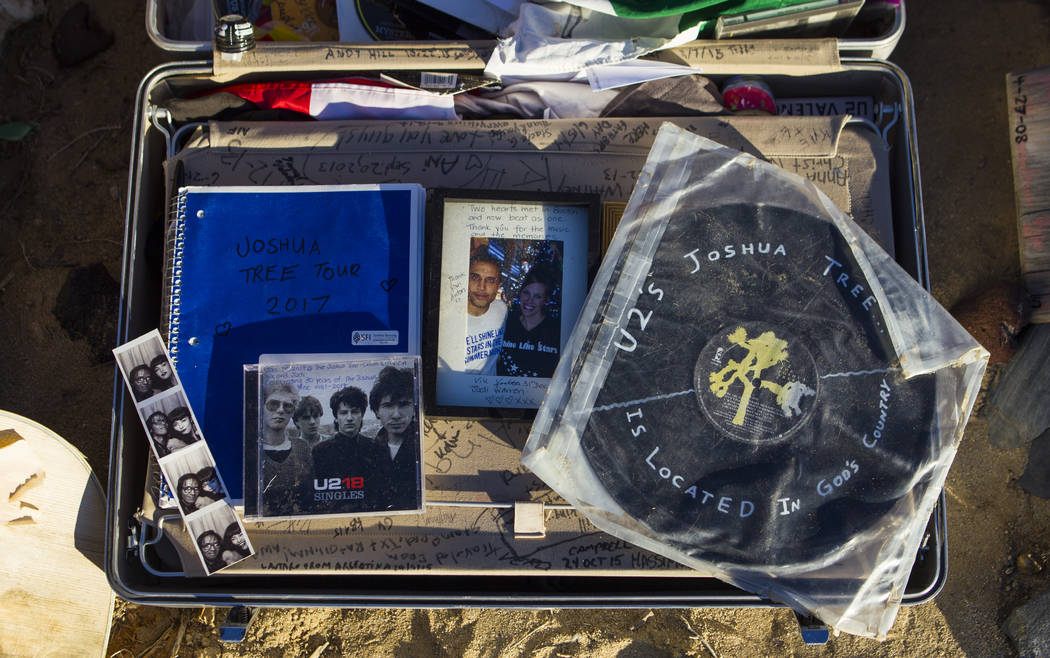 """A briefcase with tributes and memorabilia from fans of rock band U2 sits with the fallen tree that appeared in the band's 1987 album """"The Joshua Tree"""" outside of Death Valley Nat ..."""