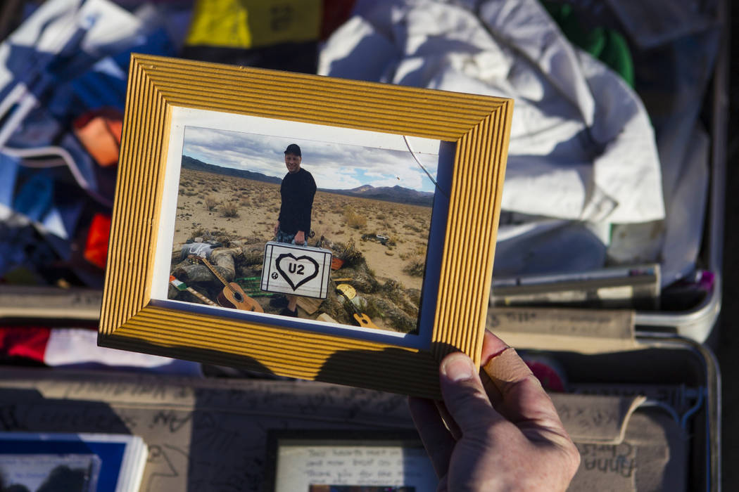 """A photo left by fans of rock band U2 sits with the fallen tree that appeared in the band's 1987 album """"The Joshua Tree"""" outside of Death Valley National Park along California Sta ..."""