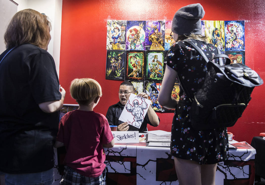Free Isabelo, middle, shows a finished illustration of Deadpool he drew for Gavyn Trudell, second from left, during a fundraising event to support local nonprofit Critical Care Comics on Thursday, ...