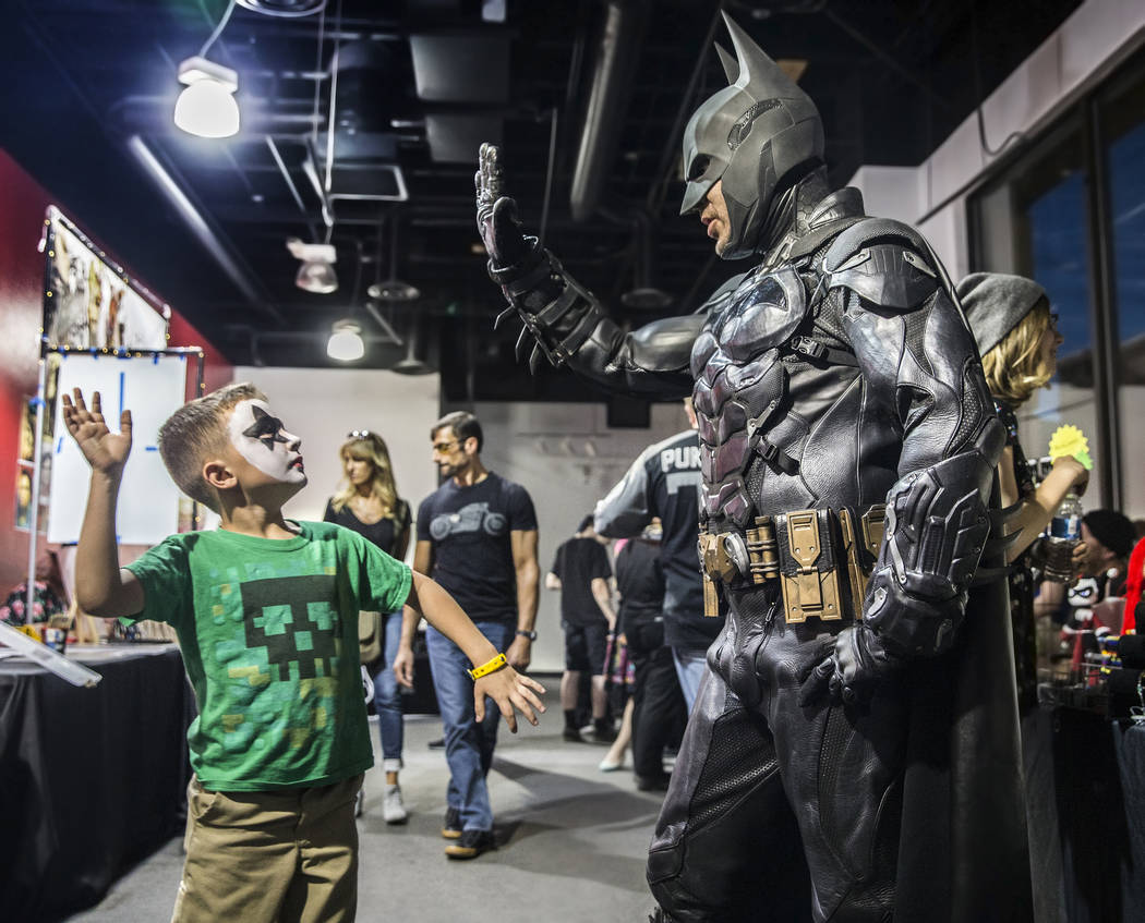Vinny Schmid, 8, gives Cody Strohl, dressed as Batman, a high five during a fundraising event to support local nonprofit Critical Care Comics on Thursday, March 17, 2017, at Village Square, in Las ...