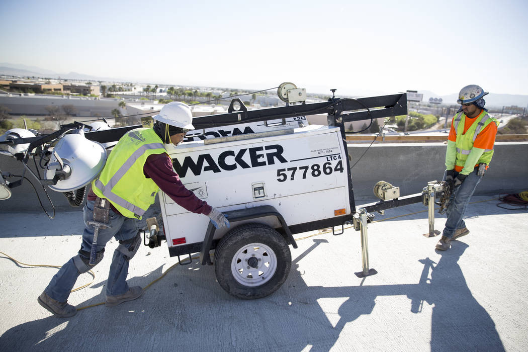 Gavino Martinez, left, and Octavio Morales move equipment at the McCarran Airport Connector construction project on Thursday, March 16, 2017, in Las Vegas. (Erik Verduzco/Las Vegas Review-Journal) ...