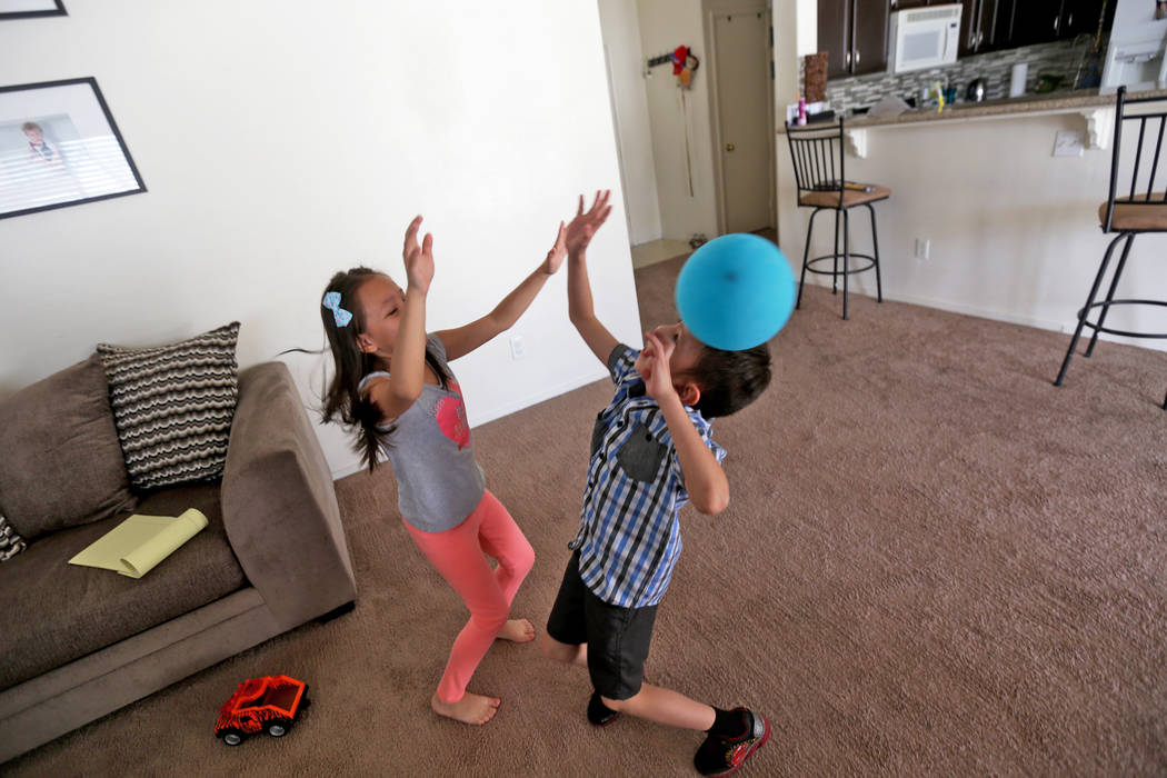 Aiden Chavez and her twin brother Abraham Chavez, 8, play with a balloon at their home on Sunday, March 19, 2017, in Las Vegas. Abraham recently had surgery to make it possible for him to smile. H ...