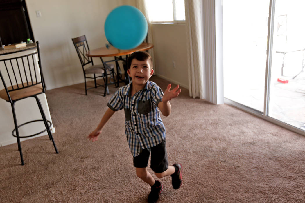 Abraham Chavez, 8, plays with a balloon at his home on Sunday, March 19, 2017, in Las Vegas. Abraham recently had surgery to make it possible for him to smile. He was born with Möebius syndrome,  ...