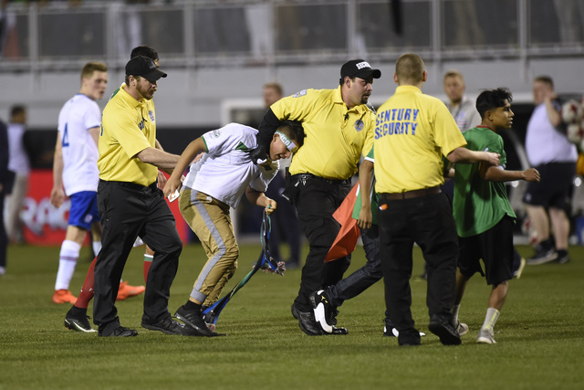 Young fans are dragged away by security after running on the field at the end of a friendly match between Mexico and Iceland Wednesday, Feb. 8, 2017, at Sam Boyd Stadium. Mexico won the game 1-0.  ...