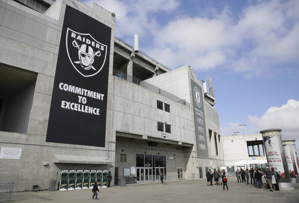 Two boys throw a football outside the Oakland Coliseum before the start of a rally to keep the Oakland Raiders from moving Saturday, March 25, 2017, in Oakland, Calif. (Eric Risberg/AP)