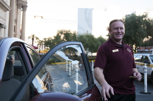 Adam Lydic, valet parking runner at the Forum Shops at Caesars Palace casino-hotel in Las Vegas, interacts with arriving guests Wednesday, Jan. 15, 2014. (Erik Verduzco/Las Vegas Review-Journal)