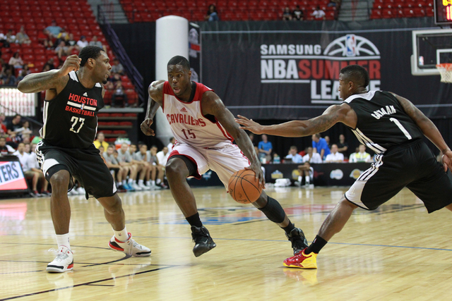 Cleveland's Anthony Bennett (15) looks to drive the ball past Houston's Tarik Black (27) and Isaiah Canaan (1) during an NBA Summer League game at the Thomas & Mack Center in Las Vegas on Thur ...