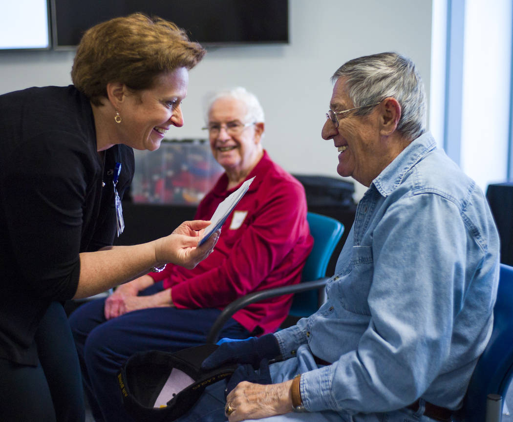 Music therapist Becky Wellman, left, holds up cards for Jerry Counter during a session for patients with memory and movement disorders at the Cleveland Clinic Lou Ruvo Center for Brain Health in L ...