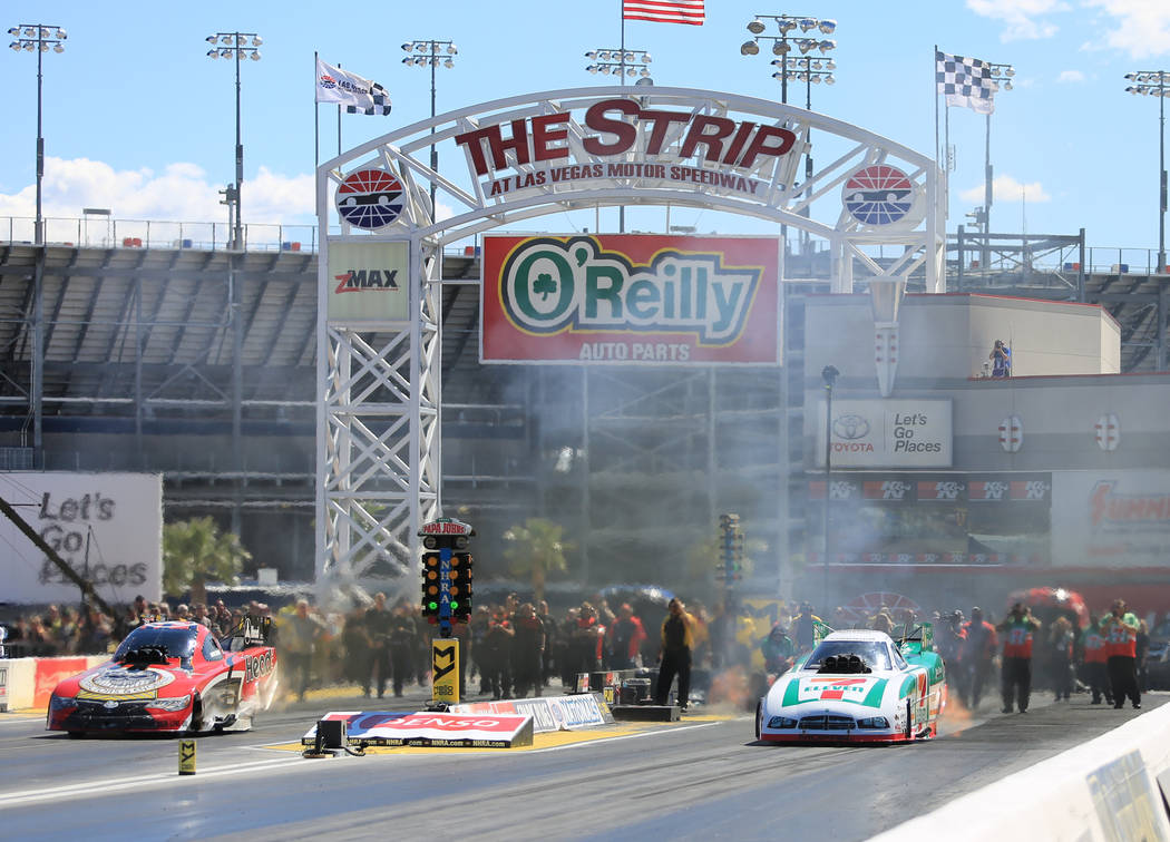 Funny Car drivers James Campbell, right lane, and Jonnie Lindberg, left lane, make a qualifying pass during the Denso Spark Plugs Nationals at The Strip at Las Vegas Motorspeedway in Las Vegas on  ...