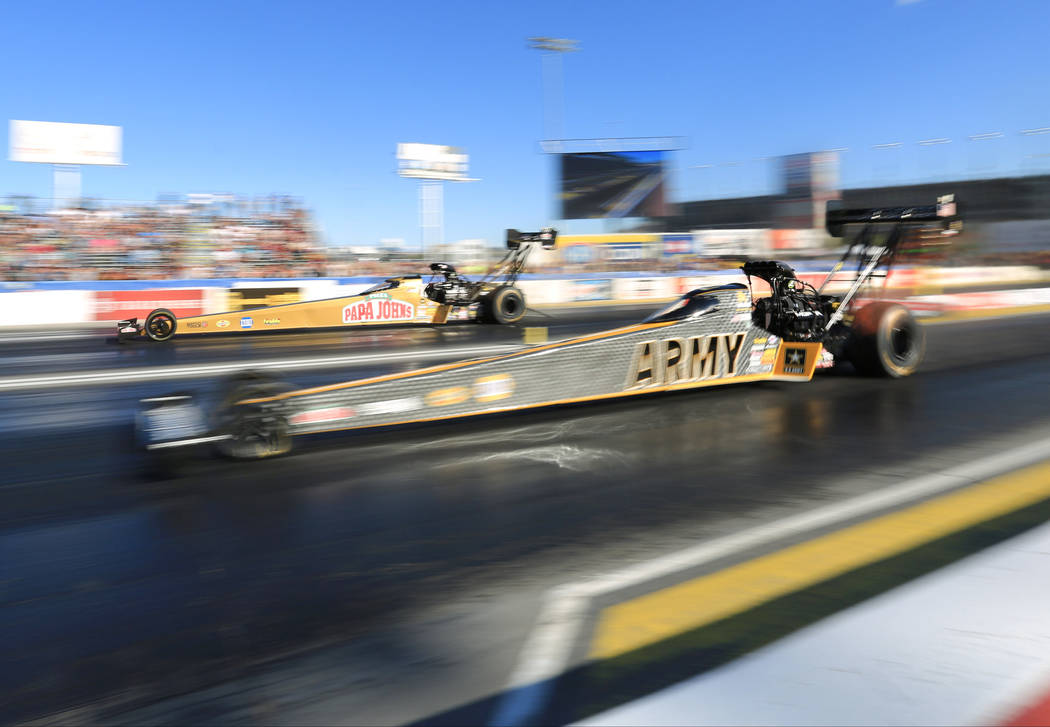 Tony Schumacher, near lane, and Leah Pritchett, far lane, face off in a qualifying pass during the Denso Spark Plugs Nationals at The Strip at Las Vegas Motorspeedway in Las Vegas on Saturday, Apr ...