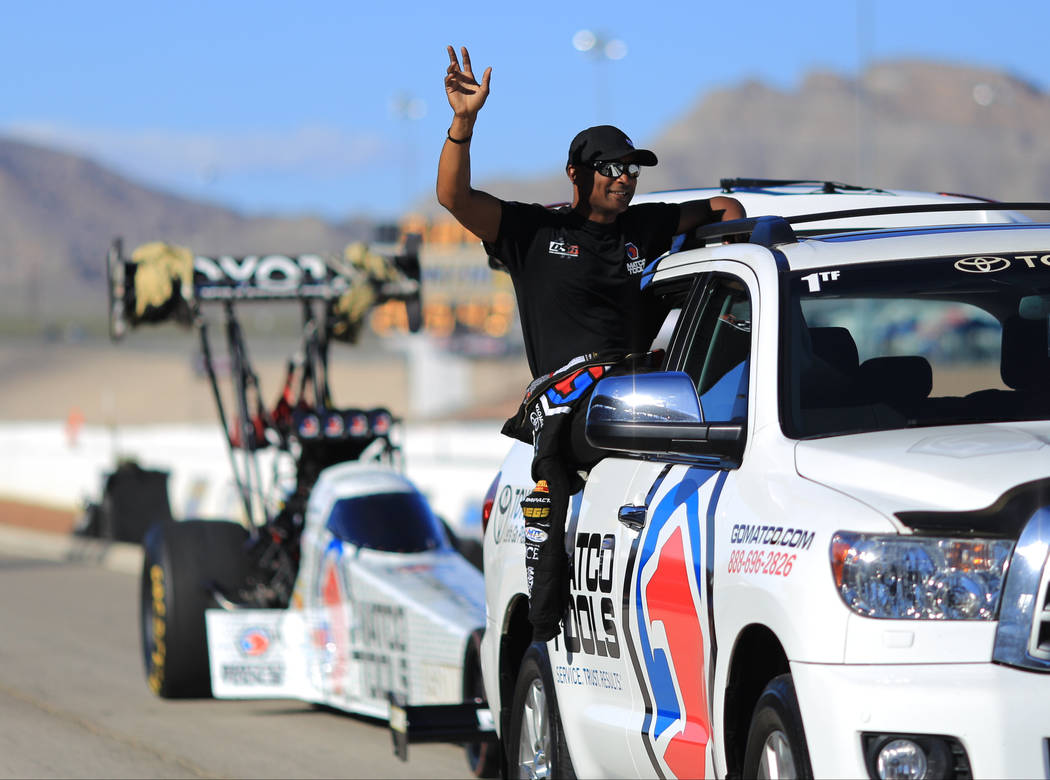 Top Fuel driver Antron Brown waves to fans while being driven back to the pits during the Denso Spark Plugs Nationals at The Strip at Las Vegas Motorspeedway in Las Vegas on Saturday, April 1, 201 ...