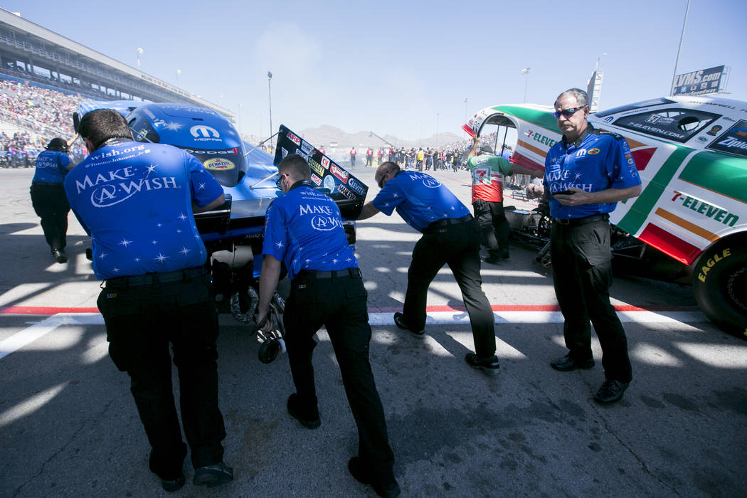 Funny Car driver Tommy Johnson Jr.'s car, left, is pushed to the start line at The Strip at Las Vegas Motor Speedway on Sunday, April 2, 2017. Johnson Jr. was named the DENSO Spark Plugs NHRA Nati ...