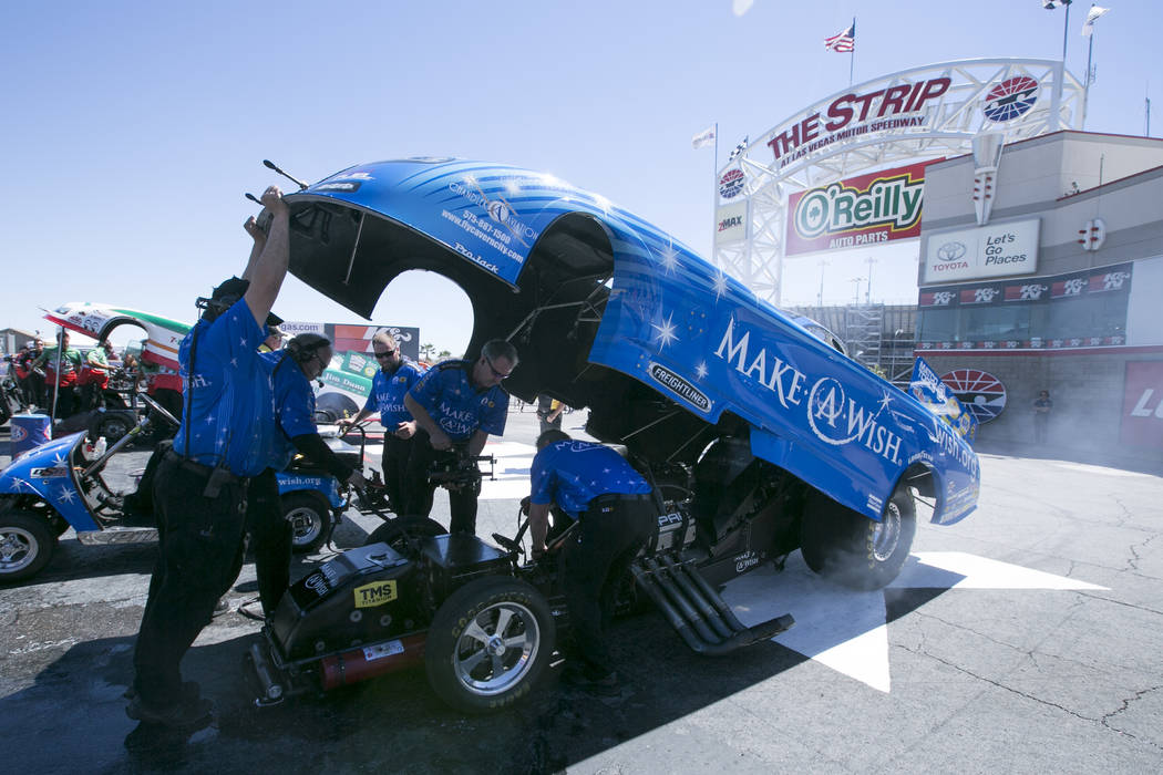 Funny Car driver Tommy Johnson Jr.'s car is worked on near the start line at The Strip at Las Vegas Motor Speedway on Sunday, April 2, 2017, in Las Vegas. Johnson Jr. was named the DENSO Spark Plu ...