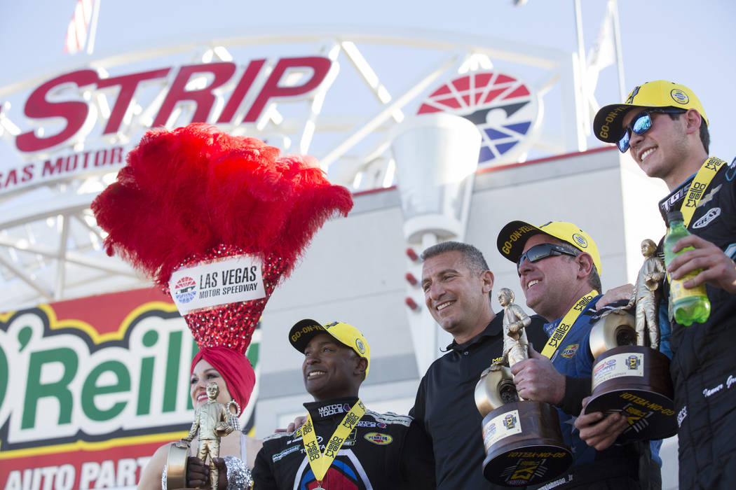 From left to right in the yellow hats Top Fuel driver Antron Brown, Funny Car driver Tommy Johnson Jr. and Pro Stock driver Tanner Gray hold their throphies at the DENSO Spark Plugs NHRA Nationals ...