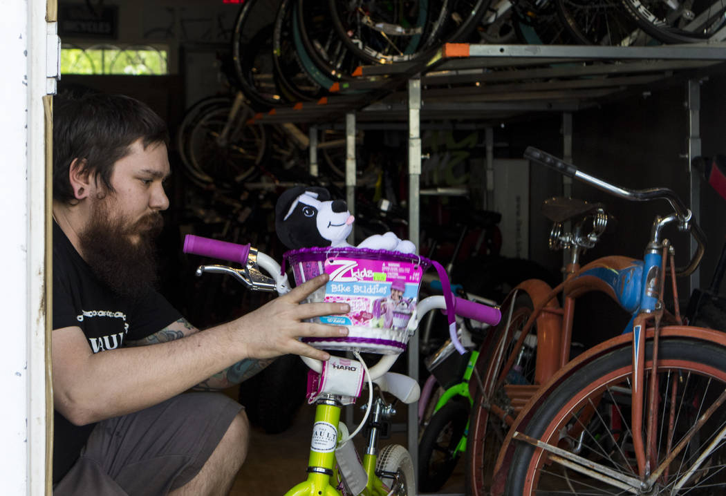 Chris Bernardi attaches a basket with a stuffed dog to a child's bike at The Vault Bicycle Shop at the Village of Centennial Springs in Las Vegas on Saturday, April 1, 2017. (Miranda Alam/Las Vega ...