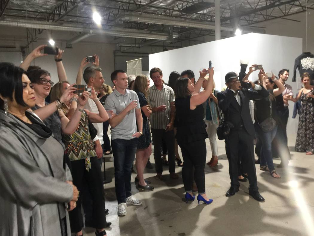 """Attendees photographing a group of artists at the """"Tilting the Basin"""" opening reception at a pop-up facility at Commerce Street in Las Vegas on March 16, 2017."""