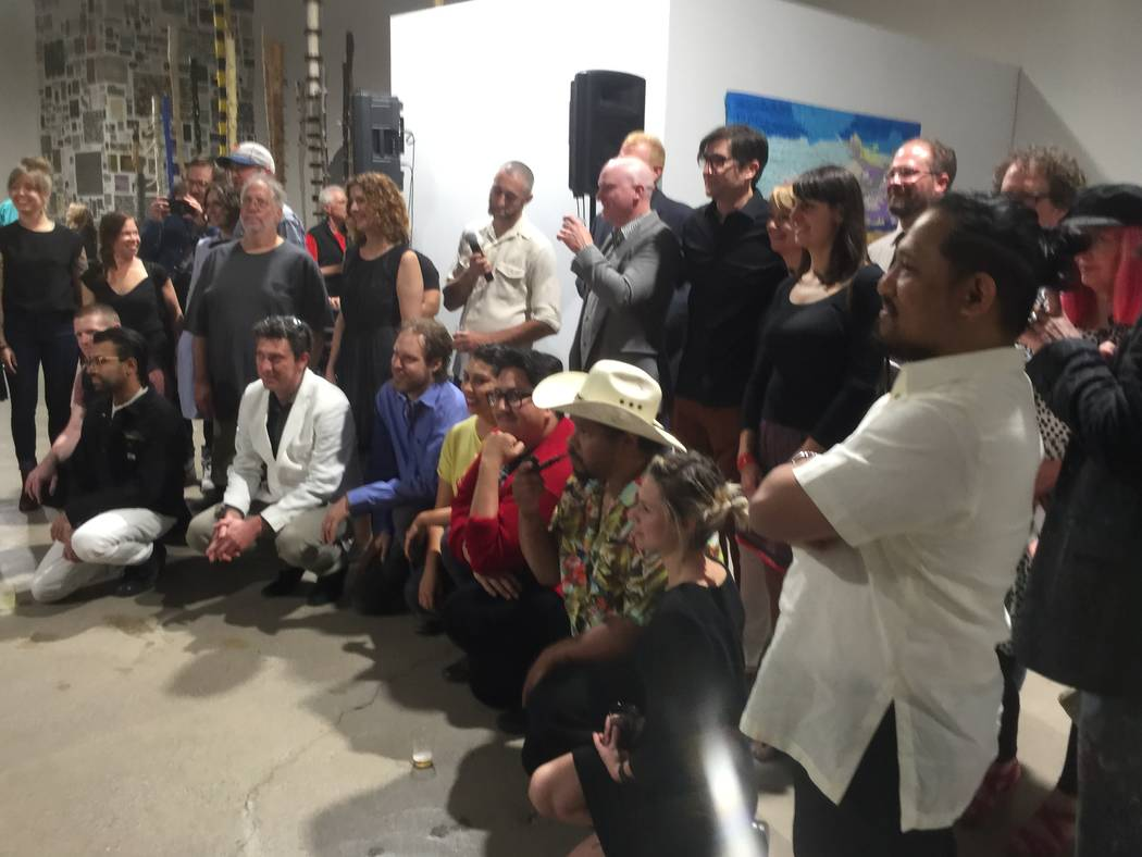 """Artists whose work is featured in the """"Tilting the Basin"""" art exhibit pose for a group portrait during the opening reception at a pop-up facility at Commerce Street in Las Vegas on March 16, 2017."""