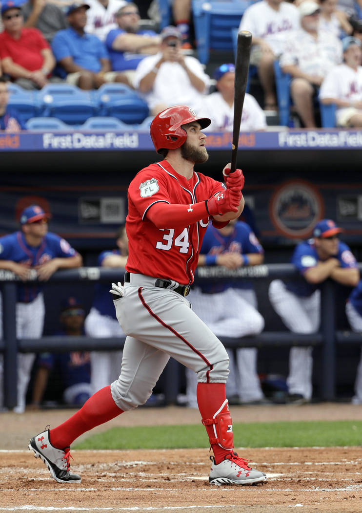 FILE- In this Feb. 25, 2017, file photo, Washington Nationals' Bryce Harper watches his home run against the New York Mets during the second inning of a spring training baseball game in Port St. L ...