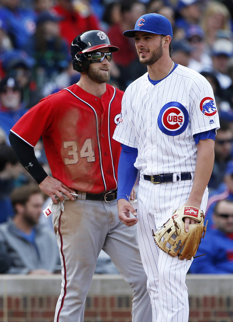 Washington Nationals' Bryce Harper, left, talks with Chicago Cubs third baseman Kris Bryant at third base during the fifth inning of a baseball game Saturday, May 7, 2016, in Chicago. (AP Photo/Na ...