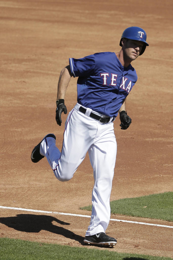 Texas Rangers' Ryan Ludwick runs home after hitting a solo home run during the second inning of a spring training baseball game against the Kansas City Royals Wednesday, March 4, 2015, in Surprise ...