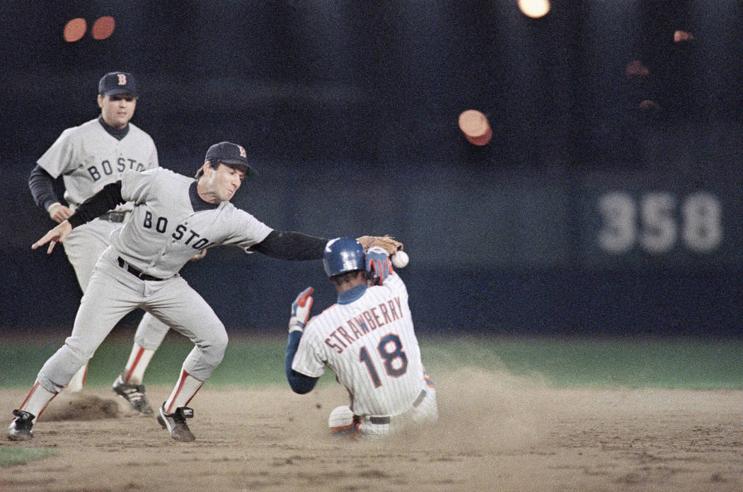 New York Mets Darryl Strawberry slides safely into second base with a stolen base in the fifth inning as Boston Red Sox Marty Barrett fields the late throw from catcher Rich Gedman as teammate Spi ...