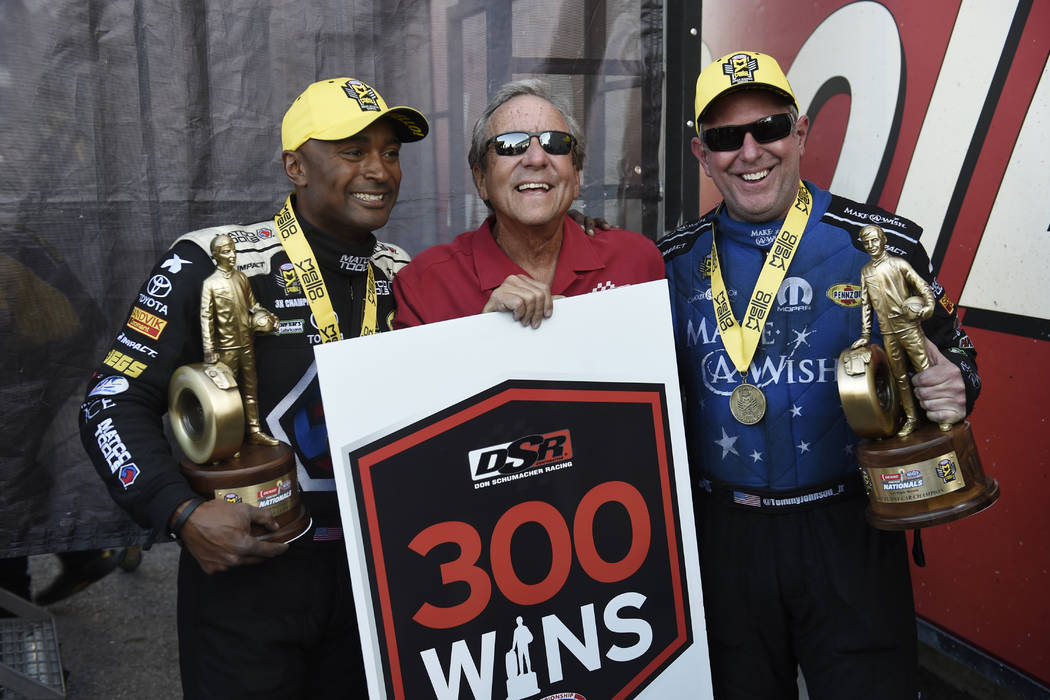 Top Fuel winner Antron Brown, left, and Funny Car winner Tommy Johnson Jr., right, pose for a photo with the owner of their teams Don Schumacher after giving Schumacher his 299th and 300th career  ...