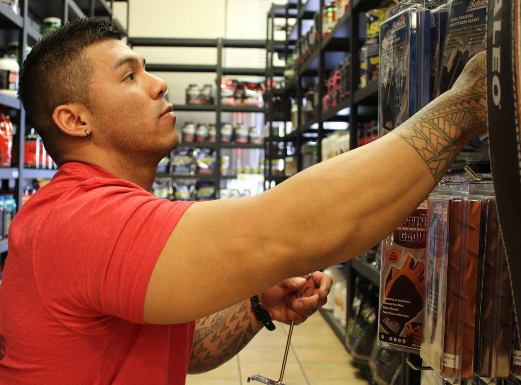 Sean Kim rearranges strength training belts at Spartan Sports Nutrition in North Las Vegas on Wednesday, March 29, 2017. (Gabriella Benavidez/Las Vegas Review-Journal) @gabbydeebee