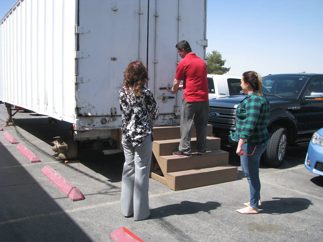 Assistant principal Derek Stafford of Las Vegas High School opens the tractor trailer that will be transformed into a distribution center for supplies for the homeless population of the school. Fr ...