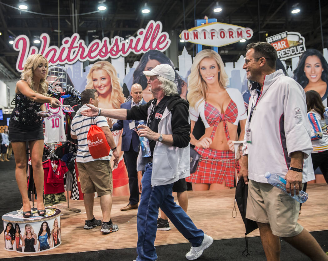 Rachel Herbert, left, hands out flyers for Waitressville Uniforms during the 2017 Nightclub & Bar Show at the Las Vegas Convention Center on Tuesday, March 29, 2017, in Las Vegas. (Benjamin Ha ...