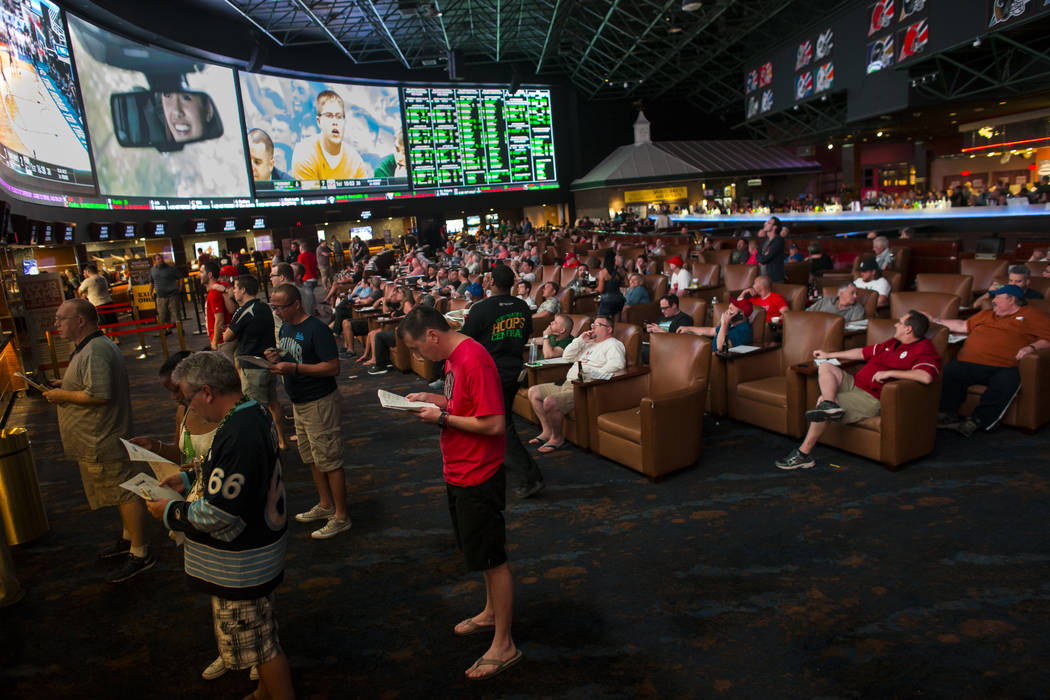 Fans line up to place bets as others watch the action during the first day of the NCAA basketball tournament at the Westgate sports book in Las Vegas on Thursday, March 16, 2017. (Chase Stevens/La ...