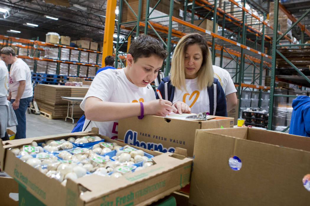Neve Eden, 12, left, and Amanda Solomon, Jewish Nevada volunteers, work for the Meals on Wheels programs on Good Deeds Day at Three Square Food Bank in Las Vegas, Sunday, April 2, 2017.(Elizabeth  ...