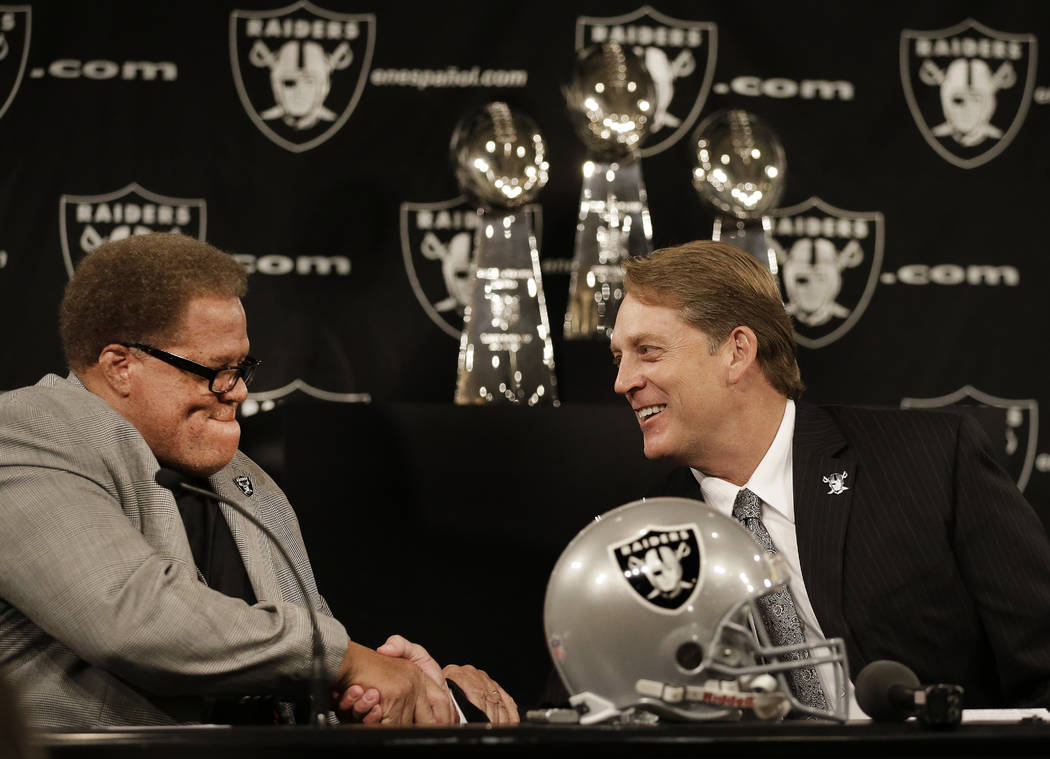 This Jan. 16, 2015, file photo shows Oakland Raiders coach Jack Del Rio, right, shaking hands with Raiders general manager Reggie McKenzie during a news conference in Alameda, Calif. After more th ...