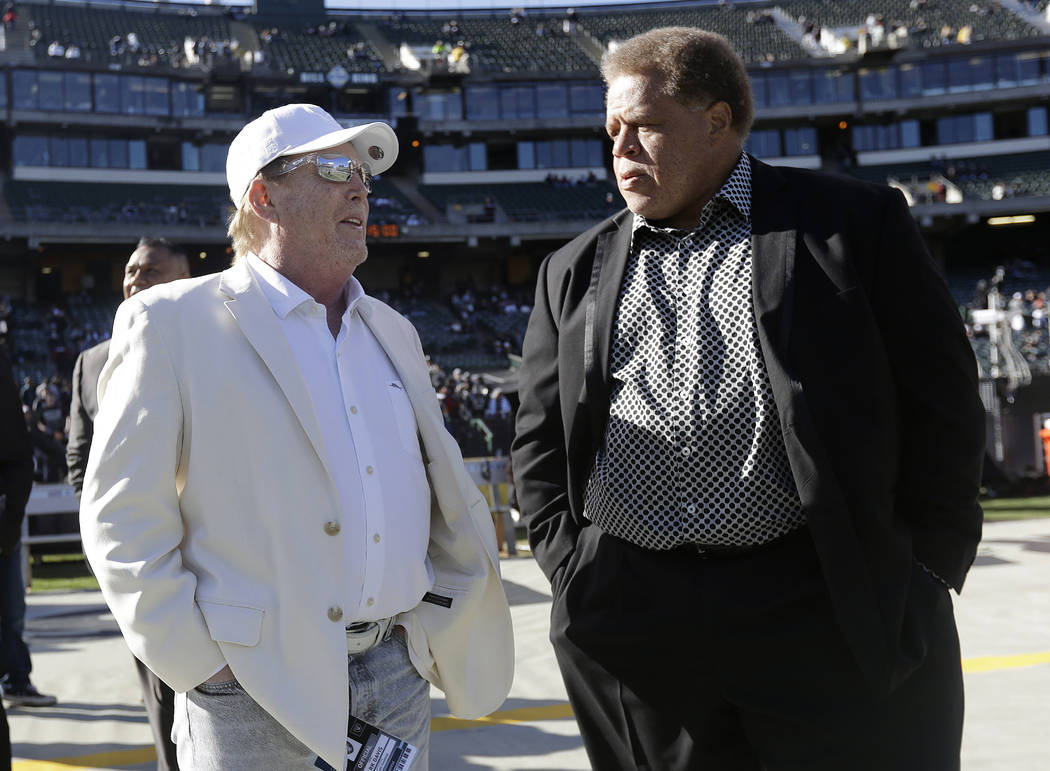 FILE - In this Saturday, Dec. 24, 2016 file photo, Oakland Raiders owner Mark Davis, left, talks with general manager Reggie McKenzie before an NFL football game against the Indianapolis Colts in  ...