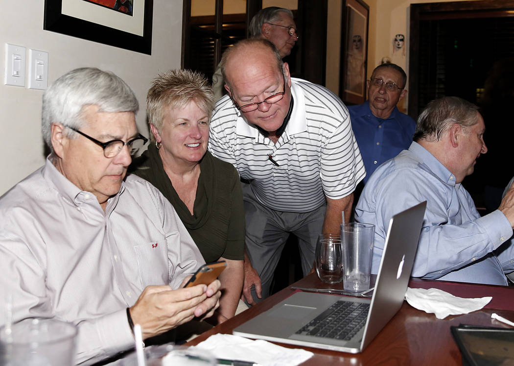 Las Vegas Ward 2 Councilman Bob Beers, center, and his campaign manager Steve Forsythe, left, monitor the result during Beers re-election watch party on Tuesday, April 4, 2017, in Las Vegas. (Bizu ...