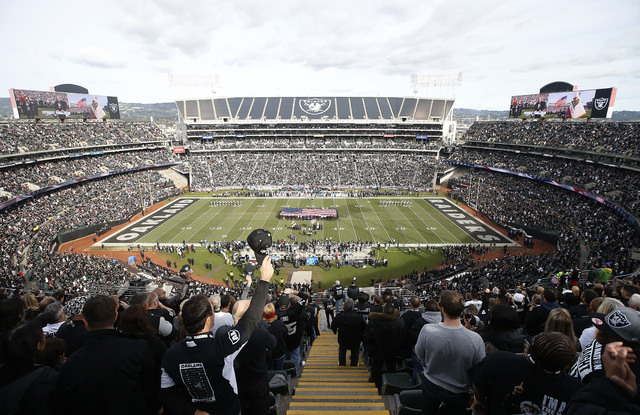 Fans watch as a flag is presented during the national anthem before an NFL football game between the Oakland Raiders and the Carolina Panthers from a general view of Oakland Alameda County Coliseu ...