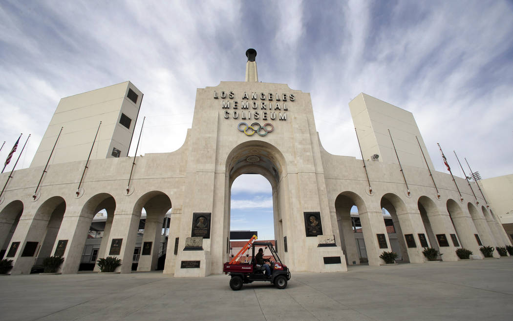 A worker rides past the entrance of The Los Angeles Memorial Coliseum on Wednesday, Jan. 13, 2016. NFL owners voted Tuesday night to allow the St. Louis Rams to move to a new stadium just outside  ...
