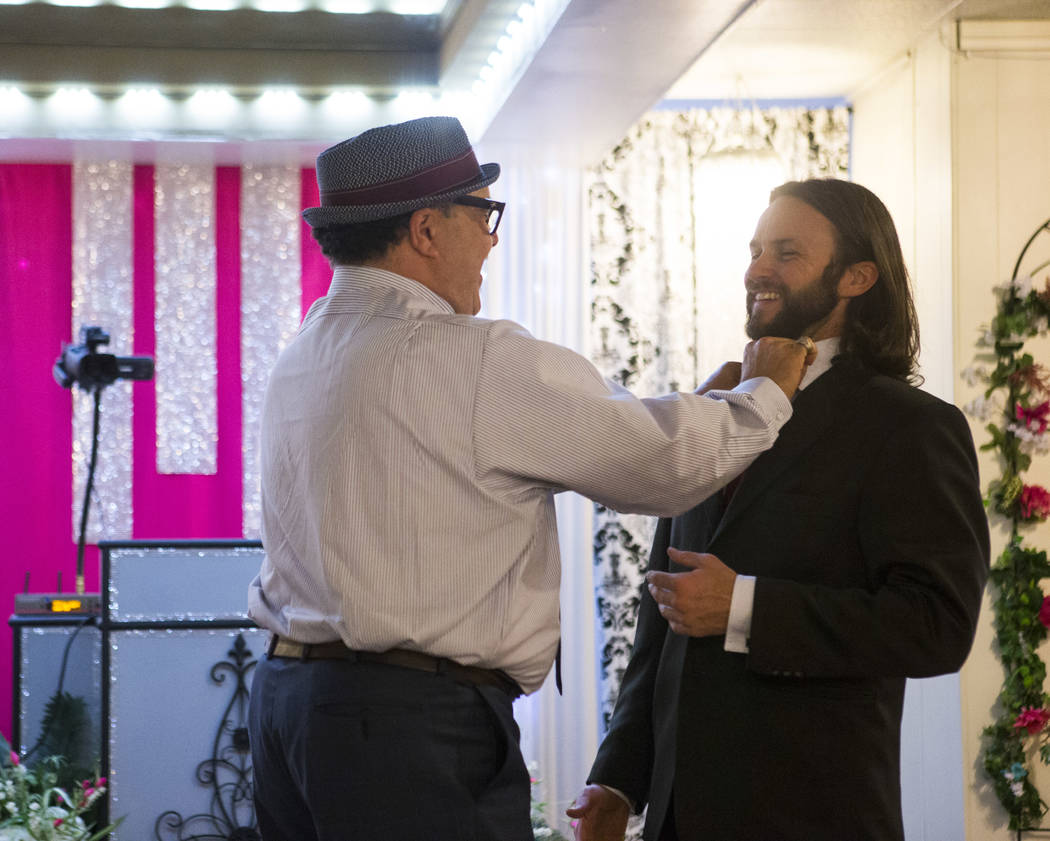 Albert Guillermo, uncle of the bride, left, adjusts the tie groom David Wenzel before his wedding at the Little Vegas Chapel in Las Vegas on Saturday, April 1, 2017. (Chase Stevens/Las Vegas Revie ...