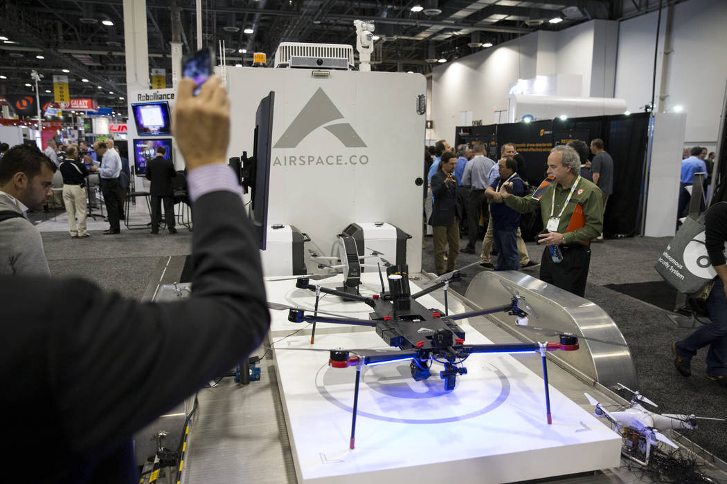 Attendees visit the Airspace booth which displayed drones capable of removing drones from the sky during on command during the International Security Conference & Exposition at the Sands Expo  ...