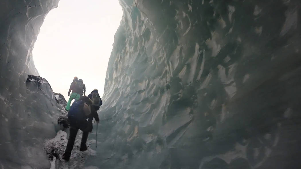 Hikers climb through a tunnel on Solheimajokull Glacier in southern Iceland. (Janna Karel/Las Vegas Review-Journal)