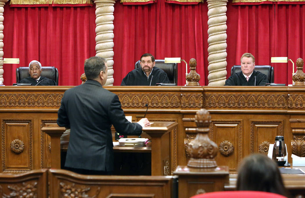 Nevada Supreme Court Justices Michael Douglas, left, Michael Cherry and Mark Gibbons hear arguments from appellate defense attorney Christopher Oram for the first time in the new Supreme Court bui ...