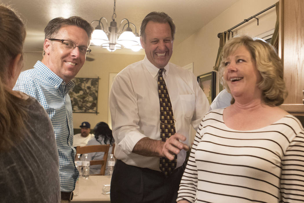 Mayor of North Las Vegas John Lee, center, with his wife Leana Lee, right, laughs as he waits for election results in the home of North Las Vegas City Council nominee Scott Black, left, on Tuesday ...