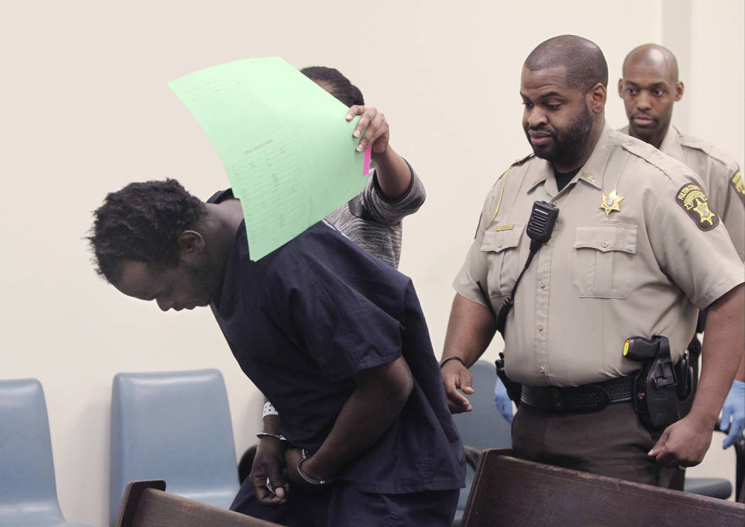 Basil Eleby sits down on the bench for his first appearance hearing at the Fulton County Jail while his public defender attempts to cover his face with a folder in Atlanta on Saturday, April 1, 20 ...