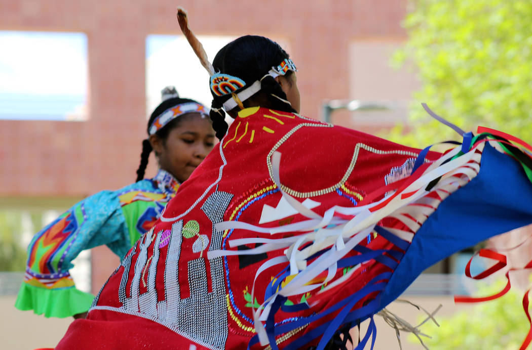 Zjustyxiazhaa Brooks, 11, in foreground, and her sister Zjustyaira, 12, of the Navajo Nation, perform a fancy shawl and jingle dress dance, respectively, during the Festival of Communities at UNLV ...