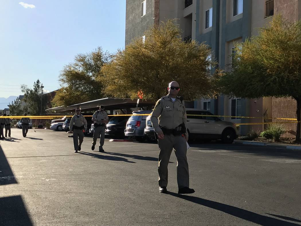 Las Vegas police officers talk to a man outside the H Street apartment complex where a woman's body was found. Police are investigating her death as a homicide. Rio Lacanlale/Las Vegas Review-Journal