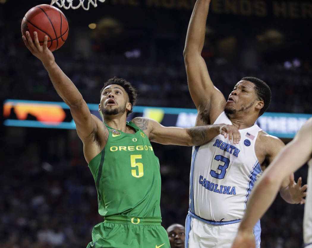 Oregon guard Tyler Dorsey (5) drives to the basket past North Carolina forward Kennedy Meeks (3) during the second half in the semifinals of the Final Four NCAA college basketball tournament, Satu ...