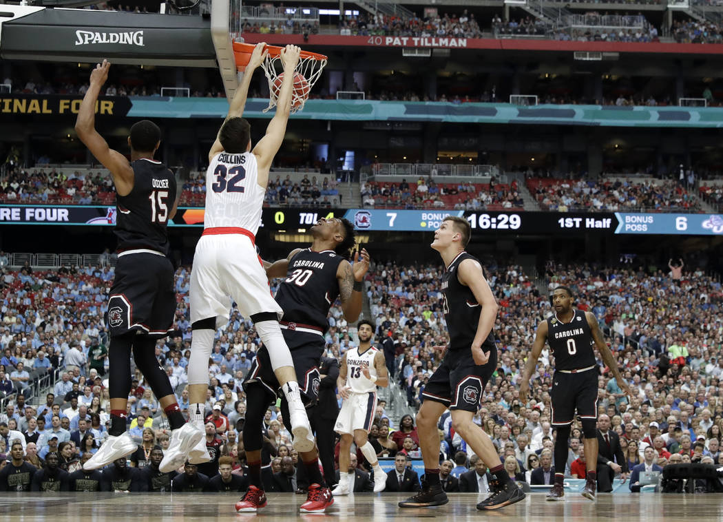 Gonzaga forward Zach Collins (32) dunks the ball over South Carolina's PJ Dozier (15) and Chris Silva (30) during the first half in the semifinals of the Final Four NCAA college basketball tournam ...