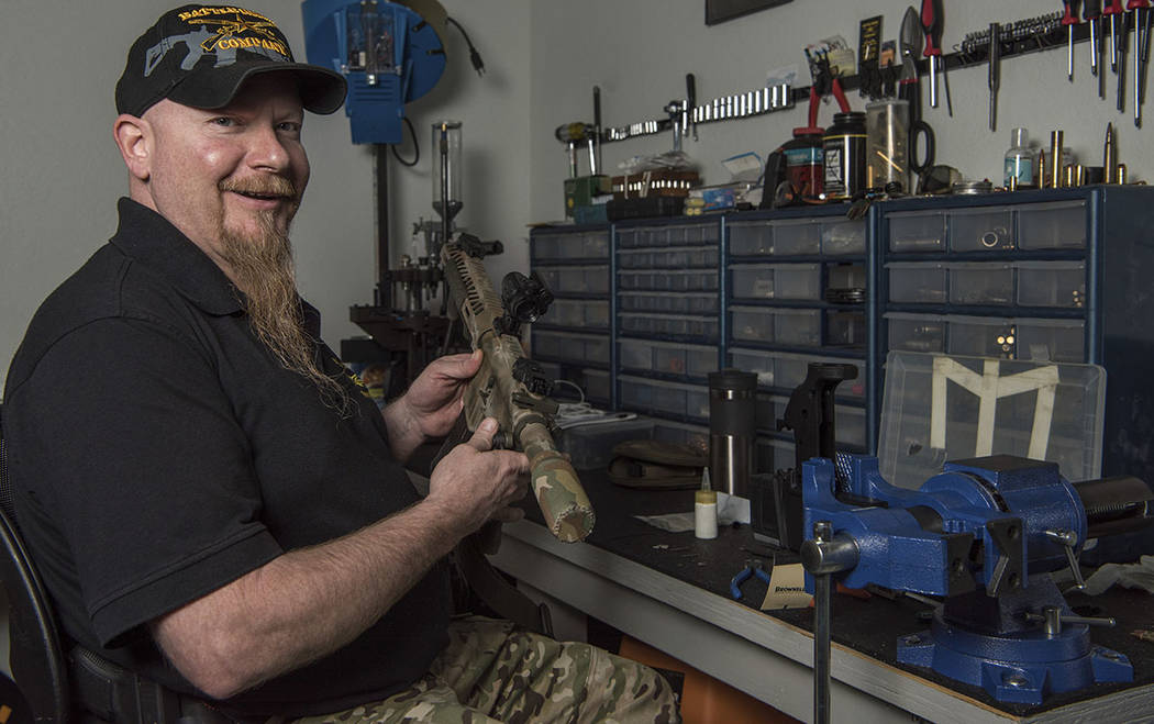 In this photo taken March 15, 2017, Jamey Spears, an ammunition expert for Battle Rifle Co. poses with a gun part in Webster, Texas. (AP Photo/Lisa Marie Pane)