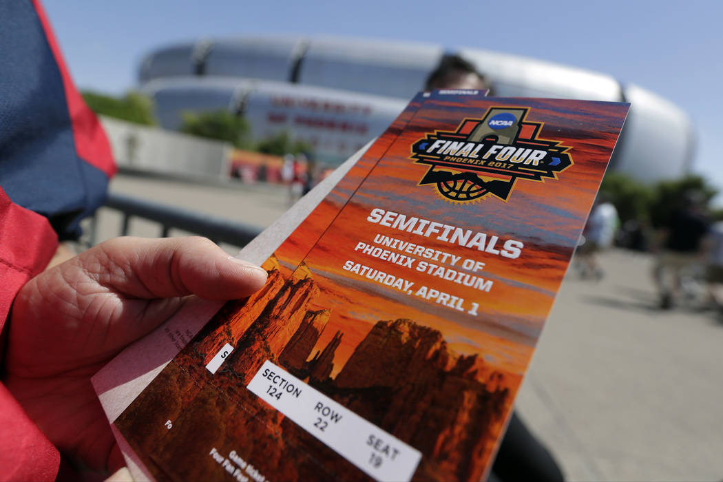 A fan holds tickets as he arrives at University of Phoenix Stadium before the semifinals of the Final Four NCAA college basketball tournament between South Carolina and Gonzaga, Saturday, April 1, ...